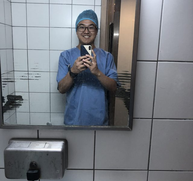 A man of East Asian appearance and wearing blue medical scrubs is smiling as he takes a photo of himself in the mirror in a white-tiled bathroom.
